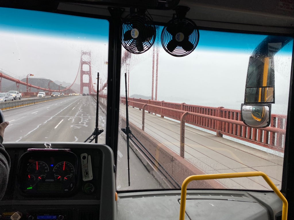 Yellow Bus crossing Golden Gate Bridge on a rainy day